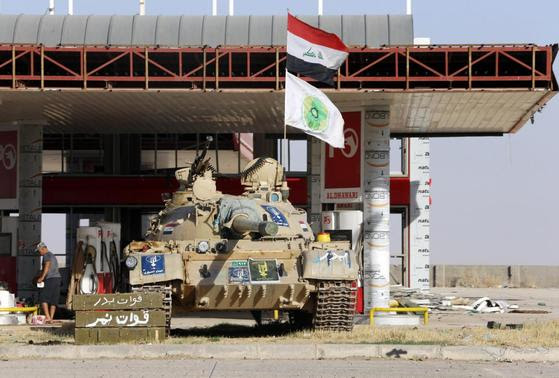 A tank belonging to the Shi'ite Badr Brigade militia takes position in front of a gas station in Suleiman Beg, northern Iraq in this September 9, 2014 file photo. REUTERS-Ahmed Jadallah-Files