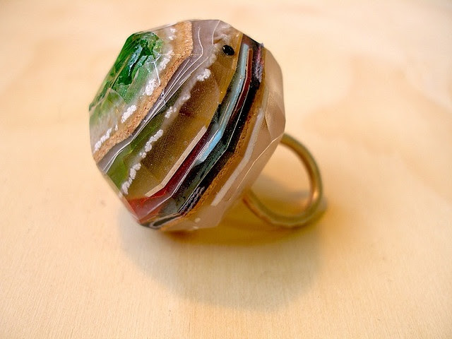 resin, layers of stuff (fabric, lino, lace, glass, bread tags, plastic flowers etc...) sterling silver. Natalia M. P.