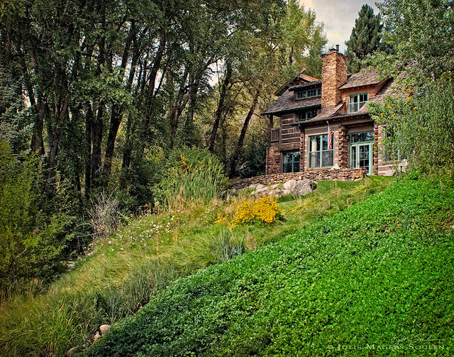 a log cabin in the woods on a hillside