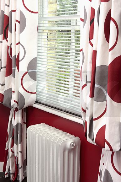 Image Close Up Of White Slatted Blind And Red Patterned Curtains On