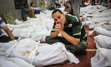 An Egyptian man sits in a mosque surrounded by bodies of protesters killed in Cairo