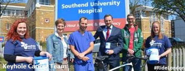 6 people in front of Southend University Hospital, 3 women and 3 men smiling one bike in front of the people