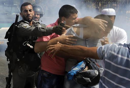Israeli border policeman uses pepper spray on a Palestinian man during clashes near Arab East Jerusalem