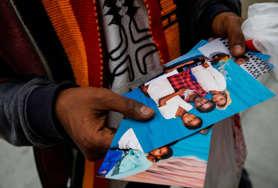 Fikre Atnafe looks through photos of the family of Yonas Alehegne, an Ethiopian immigrant who was shot and killed by an Oakland police officer in August, at a candlelight vigil for him in Oakland, Calif., on Sunday, September 13, 2015. Photo: Sarah Rice, Special To The Chronicle
