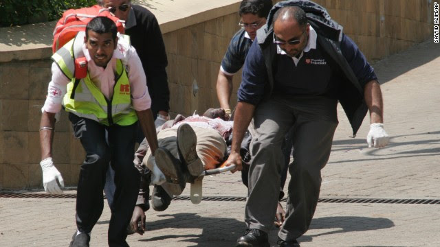 Medical personnel carry a body away.