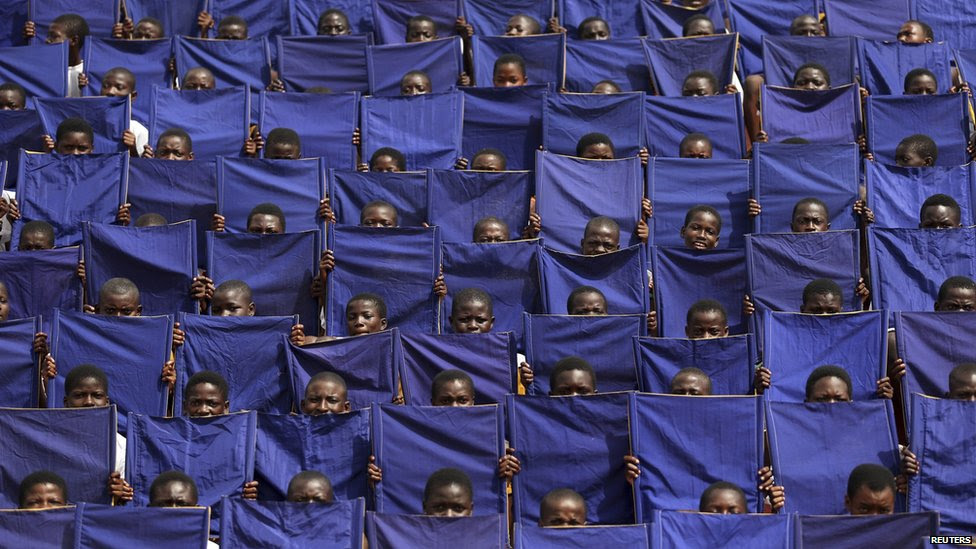 Children holding up purple flags during a parade rehearsal, Osogbo, Nigeria - Wednesday 26 November 2014