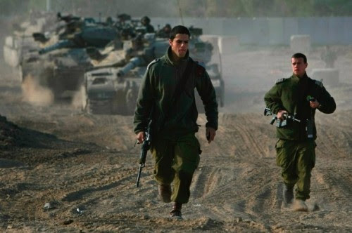 Israeli army officers run past a pair of tanks manoeuvring at their forward base on the border with the Gaza Strip on December 19, 2008 near Kibbutz Nahal Oz in southern Israel. A six-month ceasefire between Israel and the militant Islamist organization Hamas ended early this morning, with senior Israeli government officials warning that a military offensive in the Gaza Strip will be unavoidable if the rocket fire from the territory continues.  (Photo by David Silverman/Getty Images)