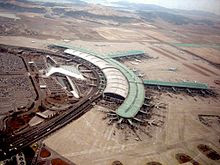 "Tilted aerial view of modern airport. Aircraft are parked next to ""arms"" that extend from the central building"