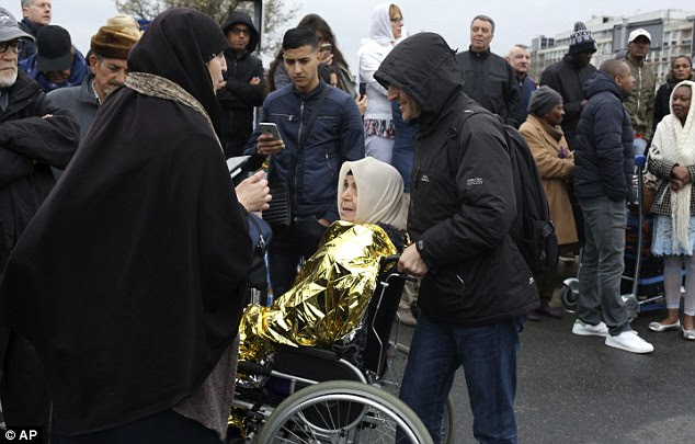 A woman in a wheelchair is helped to evacuate Orly airport this morning after the security alert