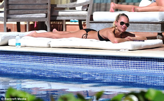 And relax: She later wore a black bikini as she lay across a sun lounger in between posing for photos