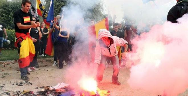 Jóvenes de ultraderecha queman estelades durante la manifestación en defensa de la unidad nacional en la plaza de Sant Jordi, en Barcelona./EFE