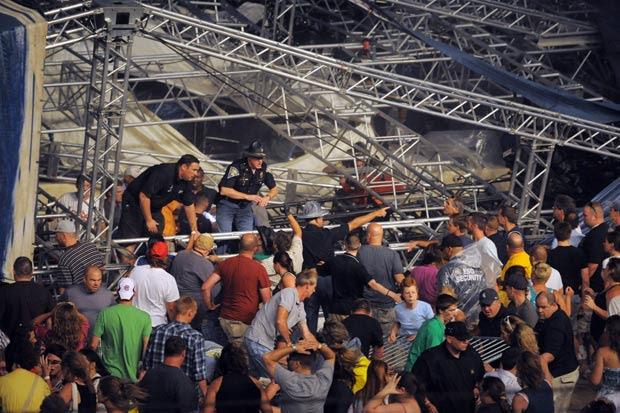 Policiais e voluntários tentam erguer ferragens após queda de palco em Indiana, nos EUA (Foto: AP)