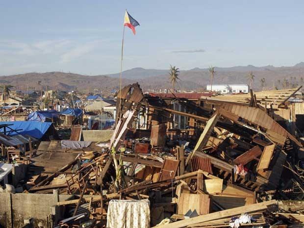 Bandeira das Filipinas hasteada em meio a uma região devastada pelo tufão. (Foto: Erik de Castro / Reuters)