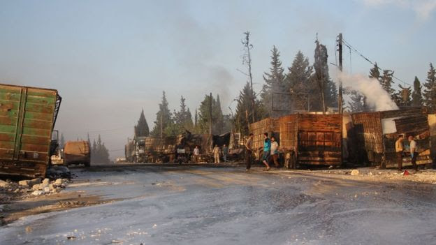 Syrians gather near damaged trucks which was part of a convoy carrying aid (20 September 2016)