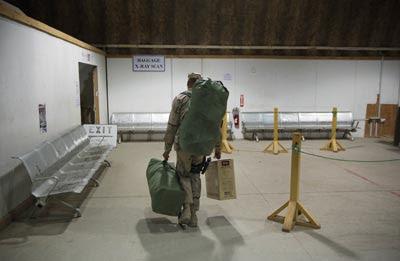 Un soldado estadounidense portando sus pertenencias en una base aérea en Bagdad antes de abandonar Irak a bordo de un avión militar. Lucas Jackson / ap