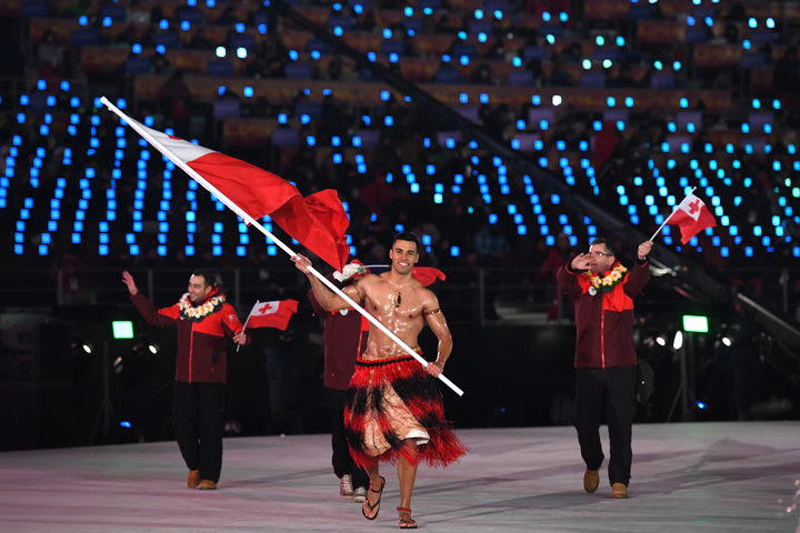 Tonga's flagbearer Pita Taufatofua leads his country's delegation.