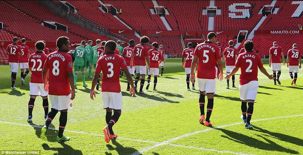 Walking away: The Manchester United players leave the Old Trafford pitch after the team picture