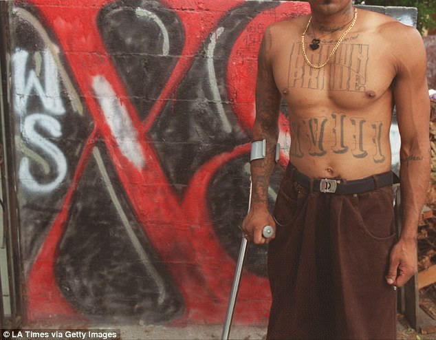 A Barrio 18 member displays his tattoos, including 'Brown Pride' and XVIII, on the gang's turf in Los Angeles. The gang has a reported presence in 20 US states