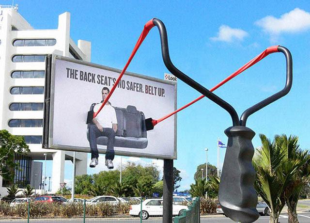 billboard with large slingshot telling backseat passengers to buckle up