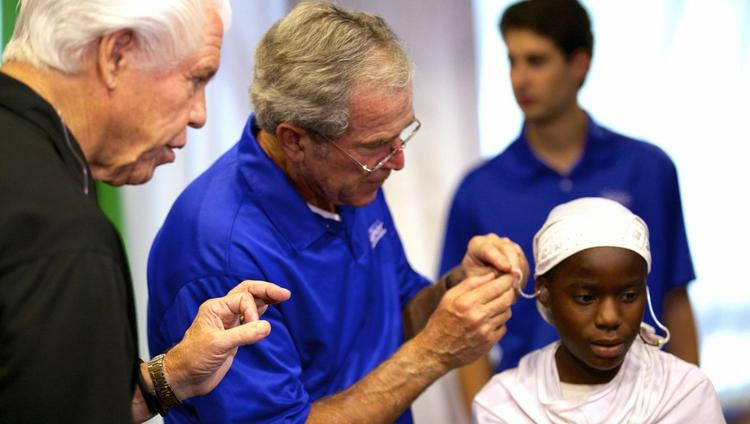 In this 2013 photo, former President George W. Bush and Starkey Hearing Technologies CEO Bill Austin give out hearing aids on a Starkey trip in Tanzania.