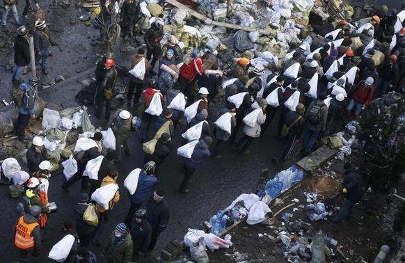 Anti-government protesters carry bags filled with stones to build barricades around the Independence Square during clashes with riot police in Kiev February 20, 2014. REUTERS-Vasily Fedosenko