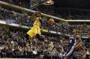 Indiana Pacers' George flies past the basket after dunking the ball in front of Memphis Grizzlies' Arthur during their NBA basketball game in Indianapolis