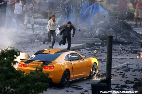 Shia and Rosie run towards Bumblebee as the Autobot comes to the rescue in TRANSFORMERS 3.