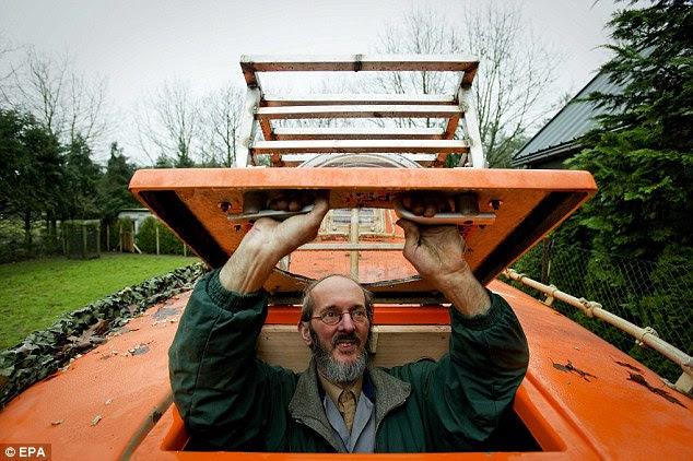 Floating Dutchman: Pieter van der Meer prepares the old Norwegian lifeboat he keeps in his back garden in Kootwijkerbroek, Holland