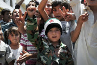 "This citizen journalism image provided by Shaam News Network SNN, taken on Friday, July 6, 2012, purports to show Syrian children chanting slogans during a demonstration in Idlib, north Syria. Syria's military began large-scale exercises simulating defense against outside ""aggression,"" the state-run news agency said Sunday an apparent warning to other countries not to intervene in the country's crisis. (AP Photo/Shaam News Network, SNN)THE ASSOCIATED PRESS IS UNABLE TO INDEPENDENTLY VERIFY THE AUTHENTICITY, CONTENT, LOCATION OR DATE OF THIS HANDOUT PHOTO"