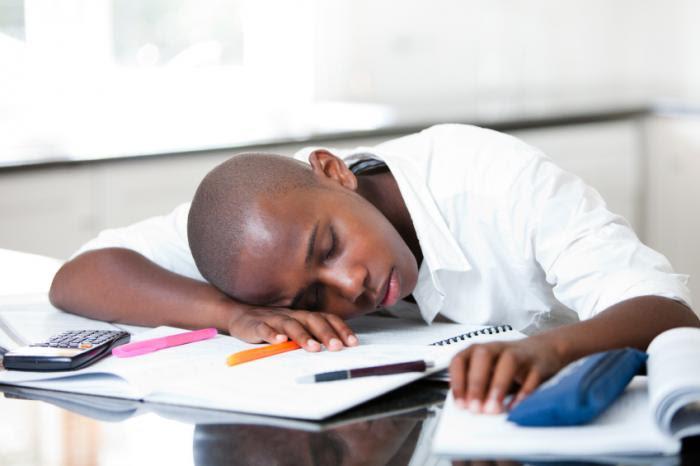 A teenager asleep on his books