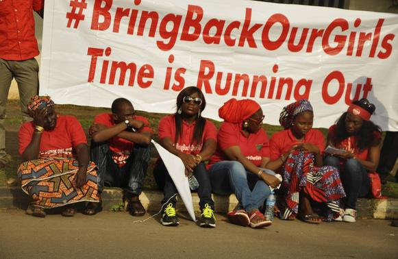 Members of the Abuja 'Bring Back Our Girls' protest group sit during a protest march, in continuation of the Global Week of Action to commemorate six months since the abduction of the 219 Chibok school girls, organized by the group to the Presidential Villa, in Abuja October 14, 2014. REUTERS-Afolabi Sotunde