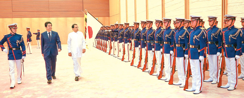 President Maithripala Sirisena inspecting the Guard of Honour at the official welcome ceremony held at the Japanese Prime Minister's Office yesterday. Japanese Prime Minister Shinzo Abe is also in the picture. Picture by Sudath Silva