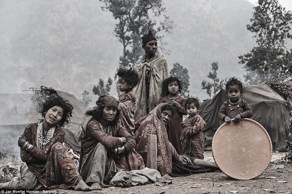 The Raute people dressed in their traditional clothing around the campsite as a child, left, holds a large, round contraption