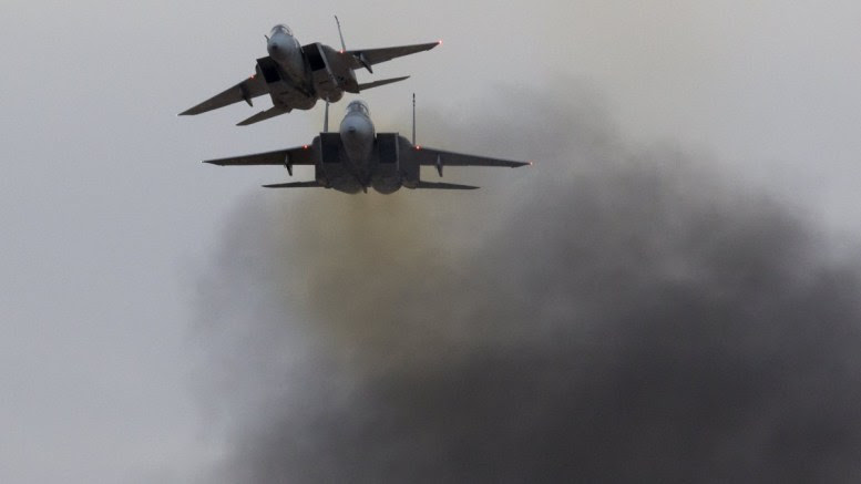 File Photo: Two Israeli Air Force F-15 fighter jets pass near a cloud of smoke burning next to the air field, during a display at Hatzerim Air Force base outside Beersheba, Israel. EPA, JIM HOLLANDER