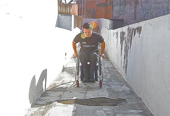 Aluno cadeirante passa por caminho esburacado em escola da zona norte de São Paulo