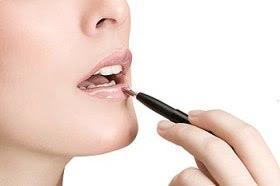 Woman applying cosmetics to her lips.