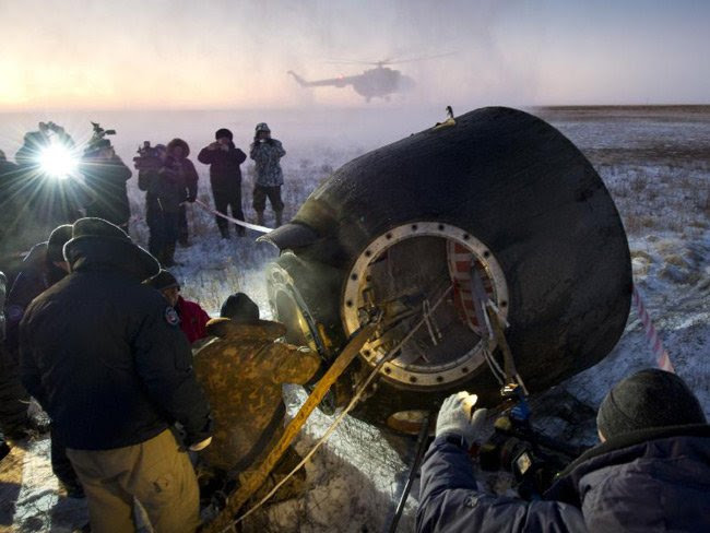 Russian support personnel work to help get crew members out of the Soyuz TMA-02M spacecraft shortly after the capsule landed with Expedition 29 Commander Mike Fossum and flight engineers Sergei Volkov and Satoshi Furukawa in a remote area outside of the town of Arkalyk, Kazakhstan, at 9:26 p.m. EST on Monday, Nov. 21, 2011. Pic: NASA/Bill Ingalls