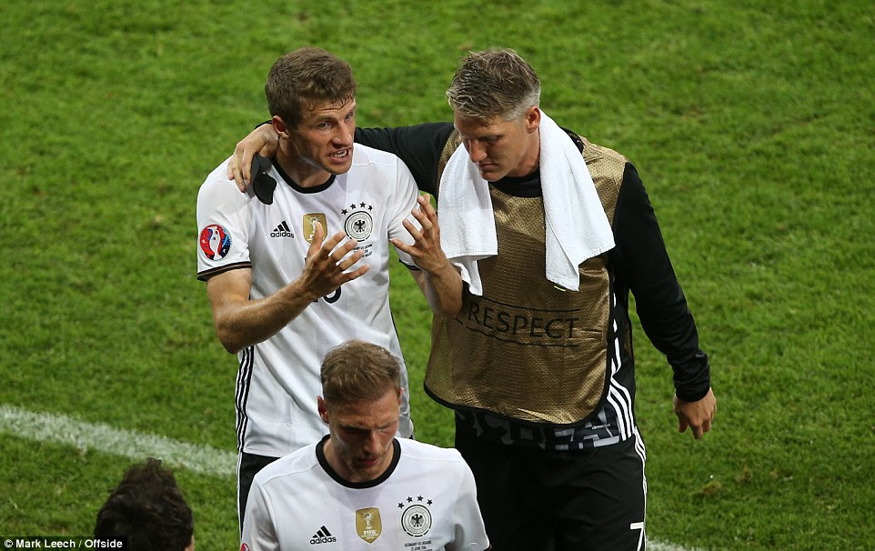 Thomas Muller of Germany is placated by then-substitute Schweinsteiger as he walks off of the pitch at half-time in Lille