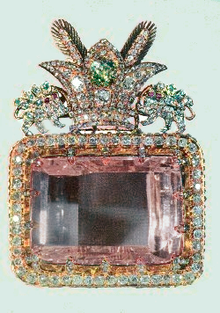 A large rectangular pink multifaceted gemstone, set in a decorative surround. The decoration includes a row of small clear faceted gemstones around the main gem's perimeter, and clusters of gems forming a crest on one side. The crest comprises a three-pointed crown faced by two unidentifiable animals.