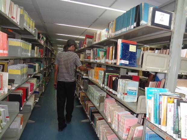 O estudante universitário percorre os corredores da biblioteca central da UFPA, que não dispõe de livros didáticos transcritos em braile para pessoas com deficiência visual. (Foto: Luana Laboissiere/G1)