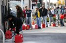 File photo of people standing in line with gas cans at a gas station on Staten Island in New York City after Hurricane Sandy