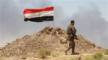 Un soldat passe près d'un drapeau irakien à Husaybah, en Irak.