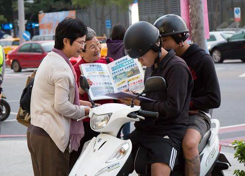 """'图2:洵姨(左二)每天到景点发传单、举真相展板,让游客明白""""法轮大法好""""。'"""