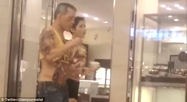The video shows the 64-year-old monarch walking through a shopping centre with a woman