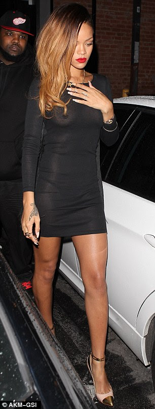 Barely there: Rihanna seemed more concerned about hiding her face from photographers rather than maintaining her modesty in the sheer dress