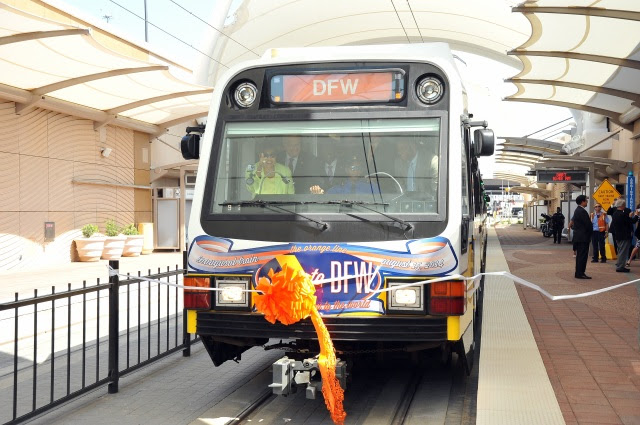A DART light rail vehicle breaks a ribbon as it enters DFW Airport Station