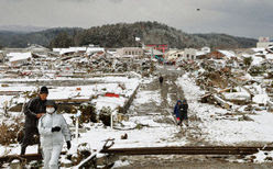 Midwinter weather in quake-hit area: People walk through snow-covered rubble in the tsunami-hit village of Noda, Iwate Prefecture, on March 16, 2011, as the temperature dropped to midwinter levels in northeastern Japan the same day. (Kyodo, used w/o permission)
