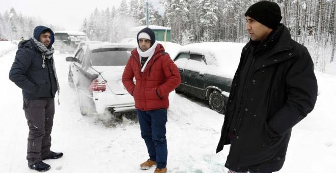 Un refugiado afgano (i) y un paquistaní (d) esperan cerca de la localidad rusa de Kuoloyarvi a poder cruzar la frontera con Finlandia, que junto a Noruega, bloqueó la ruta del Ártico en 2016 - AFP