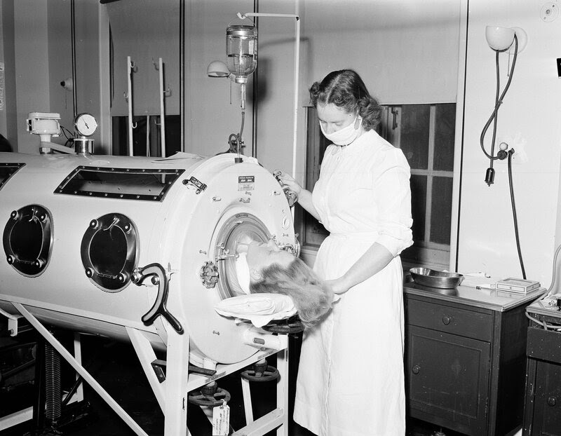A nurse assists a 27-year-old patient in an iron lung in Syracuse, N.Y., in 1954.