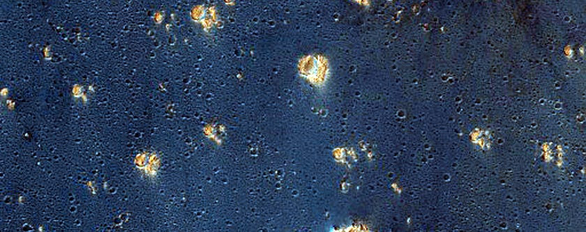 False colors assigned to certain minerals make Syria Planum an inky blue that's speckled with gold.